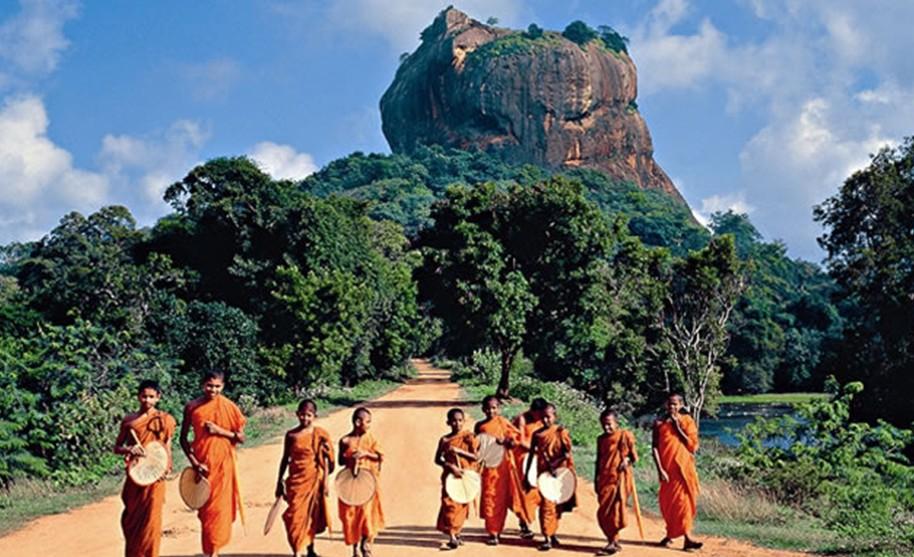 Mniši a Sigiriya Rock Fortress v pozadí