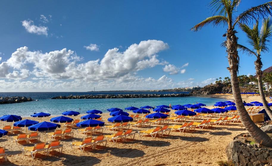 Lehátka a slunečníky na pláži na Lanzarote na Kanárských ostrovech