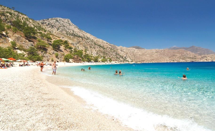Nádherná písečná pláž, hory a průhledné modré moře na Karpathosu