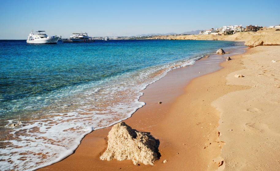 Písečná pláž a průhledné modré moře v Sharm El Sheikh v Egyptě
