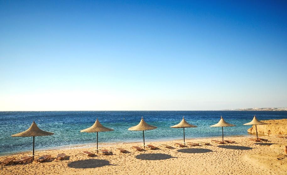 Slunečníky a lehátka na písečné pláží v Sharm El Sheikh v Egyptě