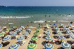 Písečná pláž se slunečníky u Nesebaru v Bulharsku
