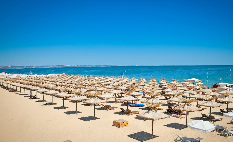 Písečná pláž se slunečníky ve Varně v Bulharsku